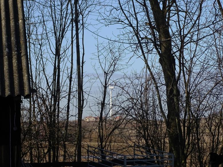 Wiatrak do produkcji prądu za drzewami