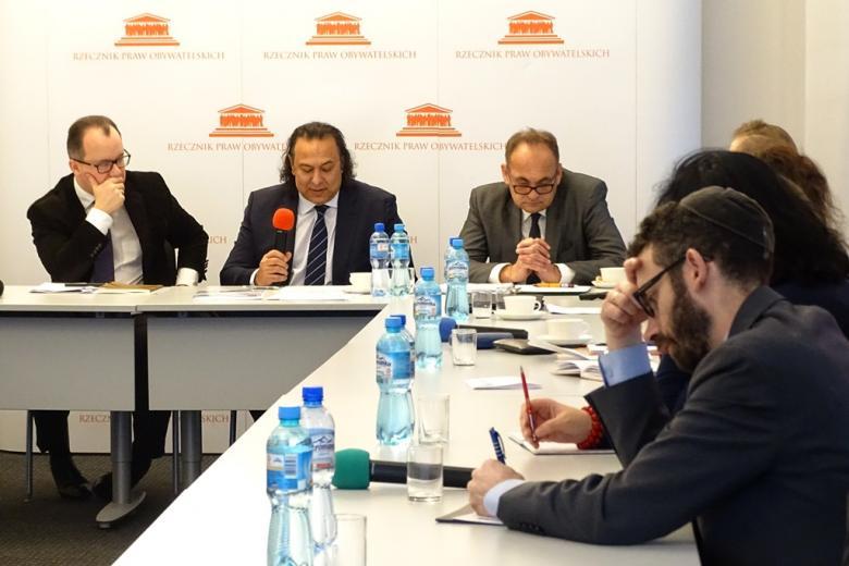 zdjęcie: kilka osób siedzi przy stołach, mężczyzna na wprost obiektywu mówi do mikrofonu