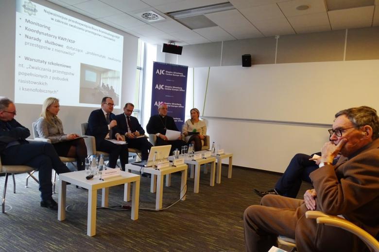 zdjęcie: po lewej stronie na foteach siedzi kilka osób, jedna z kobiet mówi do mikrofonu