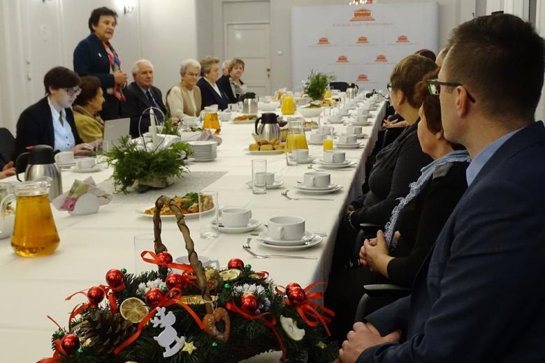zdjęcie: kilkanaście osób siedzi przy stole, jedna z kobiet stoi