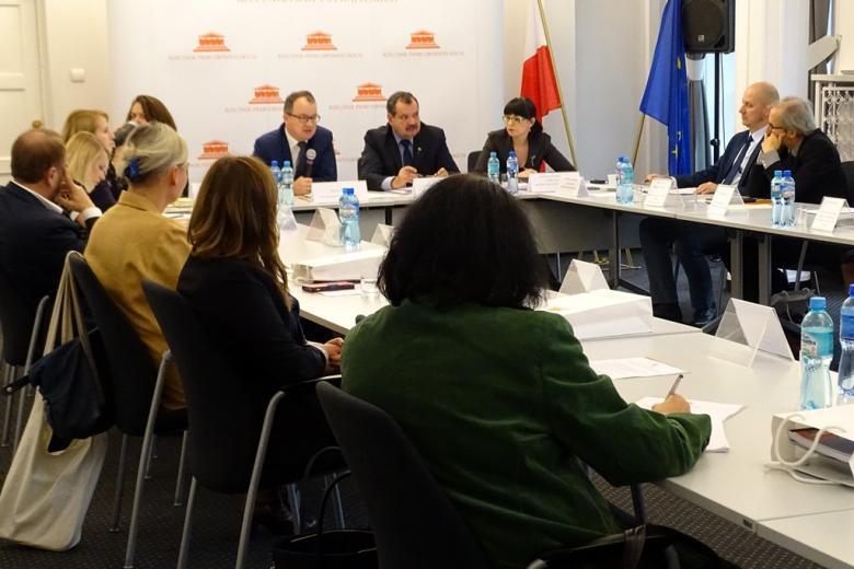 zdjęcie: kilkanaście osób siedzi przy białych stołach