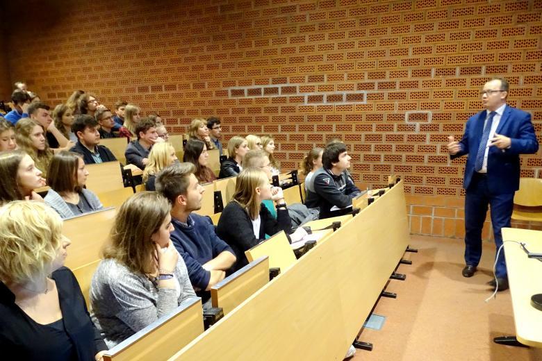 zdjęcie: mężczyzna w garniturze stoi po lewej stronie, przednim kilkadziesiąt osób siedzi na auli wykładowej