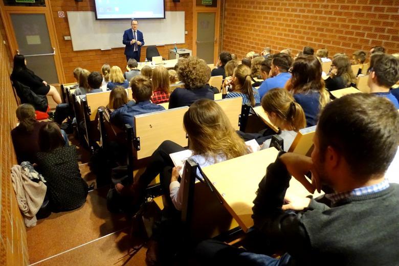 zdjęcie: kilkadziesiąt osób siedzi na auli wykładowej, niektórzy siedzą na schodach