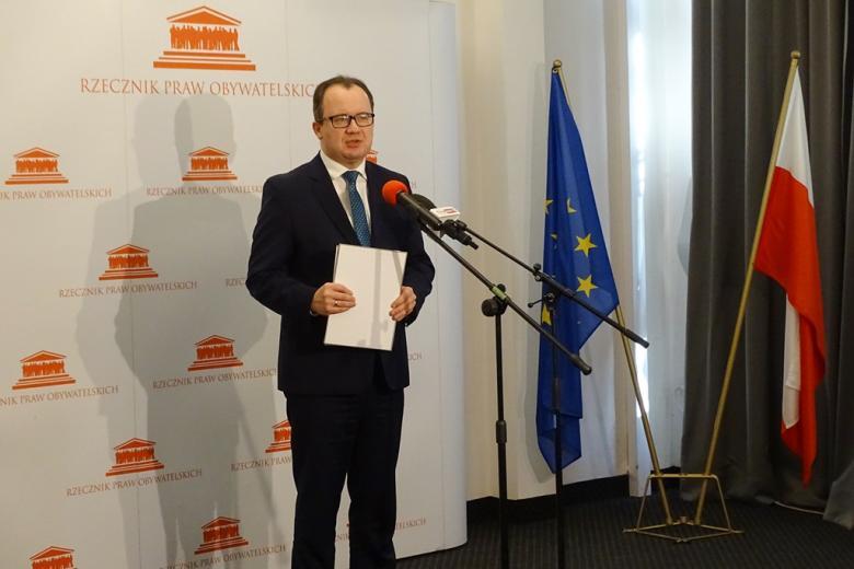 zdjęcie: mężczyzna w garniturze trzyma teczkę w ręku, w tle stoi flaga Polski i Unii Europejskiej