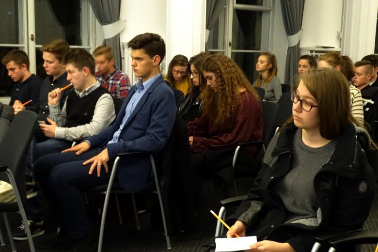zdjęcie: kilkanaście osób siedzi na krzesłach, trzymają w ręku kartki