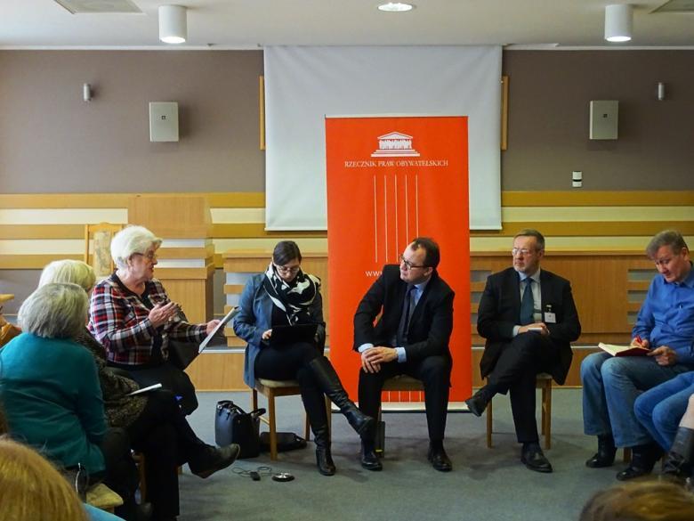Zdjęcie: uczestnicy spotkania rozmawiają z Adamem Bodnarem, który siedzi na tle pomarańczowego loga RPO