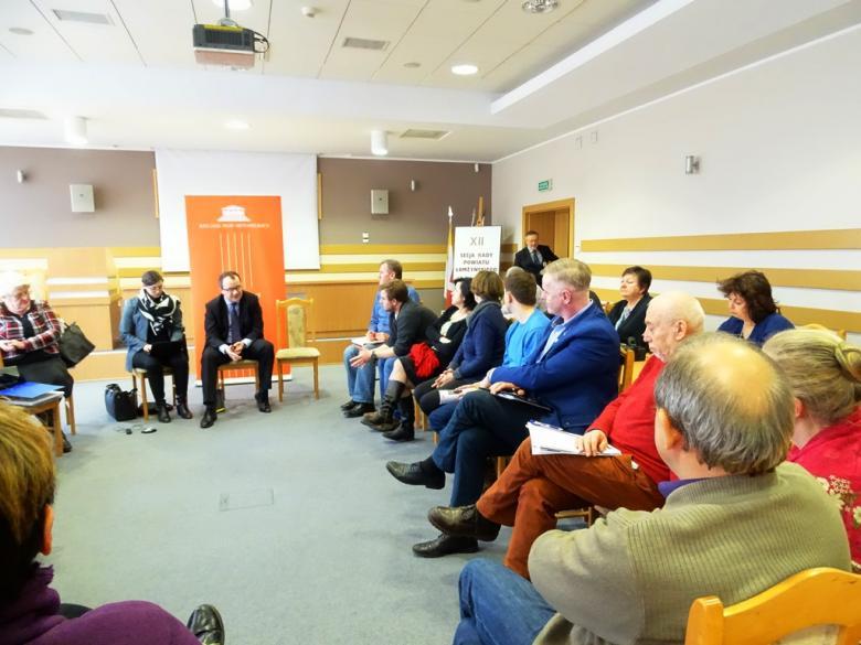 Zdjęcie: widac cała salę, uczestnicy spotkania siedzą w kręgu