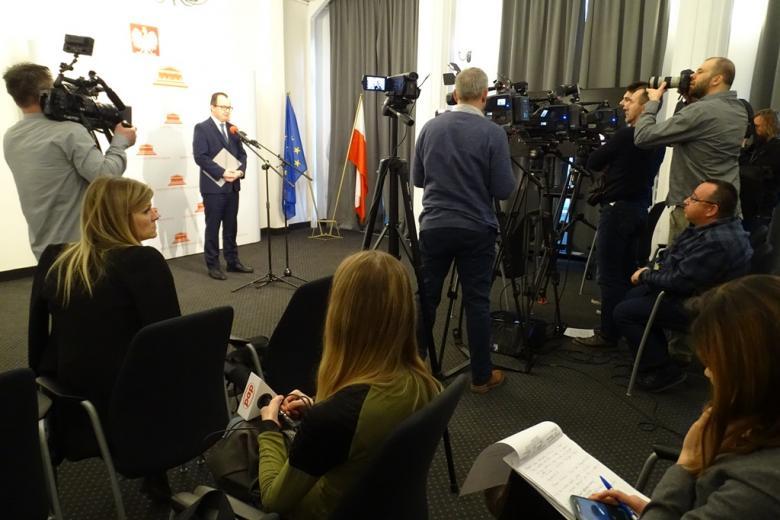 zdjęcie: mężczyzna w garniturze stoi na środku sali przed nim kilka kamer i kilkanaście osób