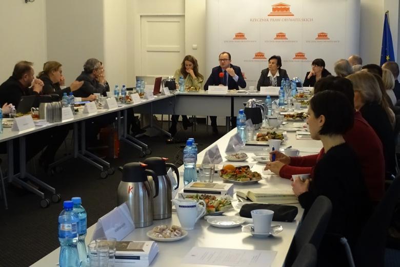 zdjęcie:kilkanaście osób siedzi przy białych stołach
