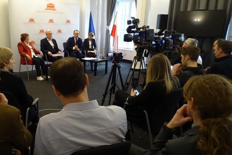 zdjęcie: dwaj mężczyźni i dwie kobiety siedzą na krzesłach, przed nimi stoją kamery i siedzi kilkanaście osób