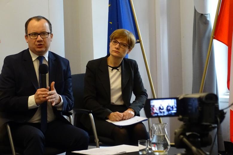 zdjęcie: mężczyzna w garniturze mówi do mikrofonu, obok niego siedzi kobieta