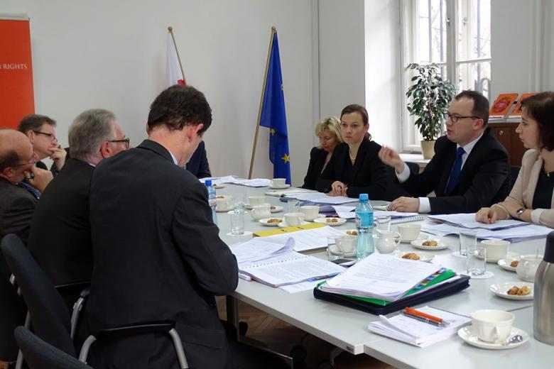 Zdjęcie: uczestnicy spotkania siedzą przy stole, przed nimi notatki