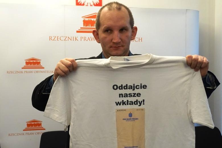 zdjęcie: mężczyzna trzyma w rękach rozłożoną koszuklkę z napisem: Oddajcie nasze wkłady