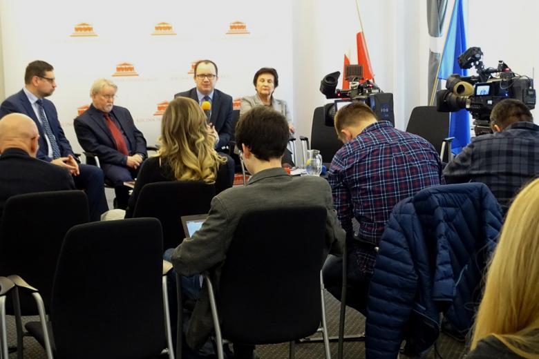 zdjęcie: trzej mężczyźni i koebiat siedzą na krzesłach przed nimi stoją dwie kamery i siedzi kilka osób