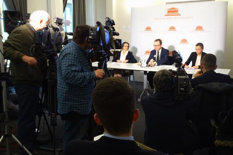 zdjęcie: za stołem siedzą trzy osoby przed nimi widać kamery i kilkanaście osób siedzących na krzesłach