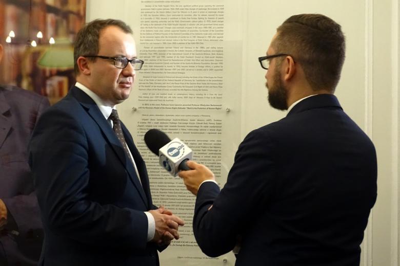 zdjęcie: dwóch mężczyz w garniturach stoi, jeden z nich trzyma mikrofon