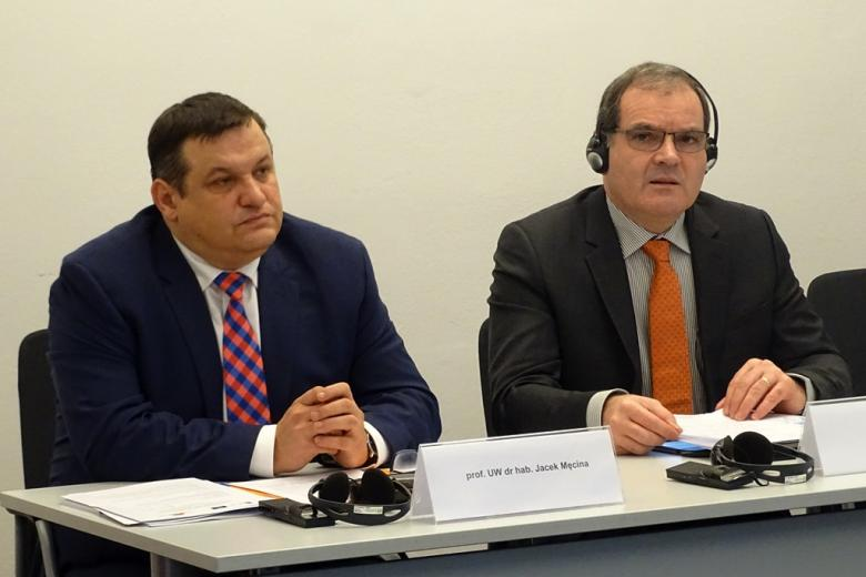 zdjęcie: dwóch mężczyzn w garniturach siedzi przy białym stole