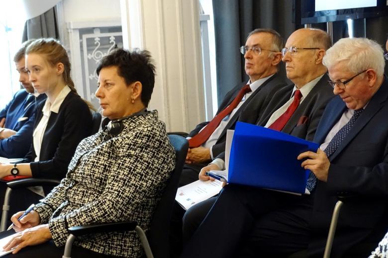 zdjęcie: na krzesłach siedzi kilka osób, przeglądają papierowy program konferencji