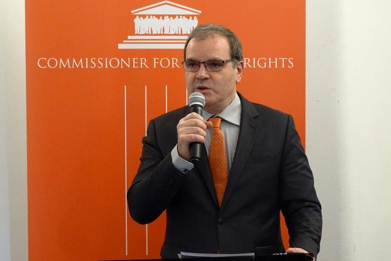 zdjęcie: mężczyzna w garniturze stoi przy mównicy i mówi do mikrofonu
