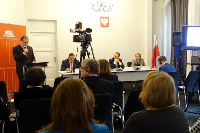 po lewej mężczyzna stojący przy mównicy po prawej stronie jest stół za którym siedzą trzy osoby