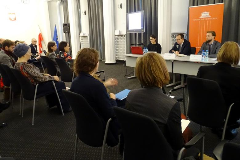 zdjęcie: kilka osób siedzi na krzesłach przed nimi jest biały stół za którm siedzi dwóch mężczyzn i jedna kobieta