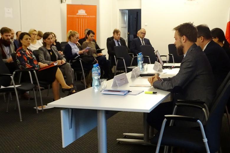 zdjęcie: po prawej stronie trzy osoby siedzą za białym stołem naprzeciw siedzi kilkanaście osób na krzesłach