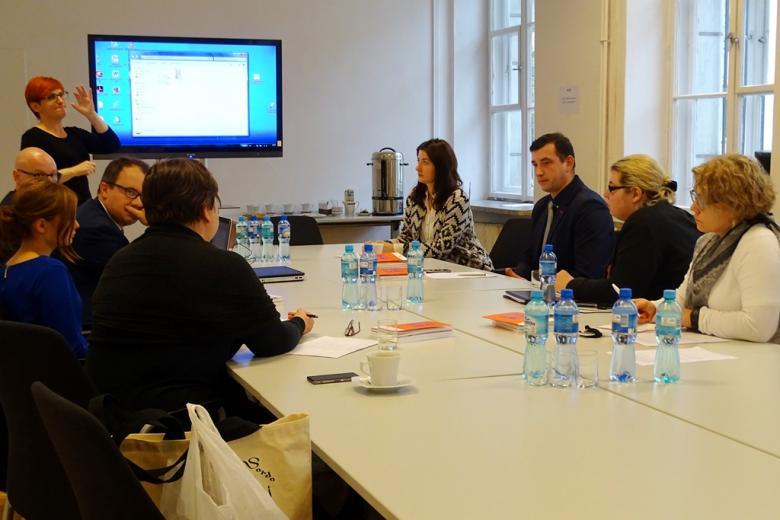 zdjęcie: kilka osób siedzi przy białtm stole za nimi jest telewizor