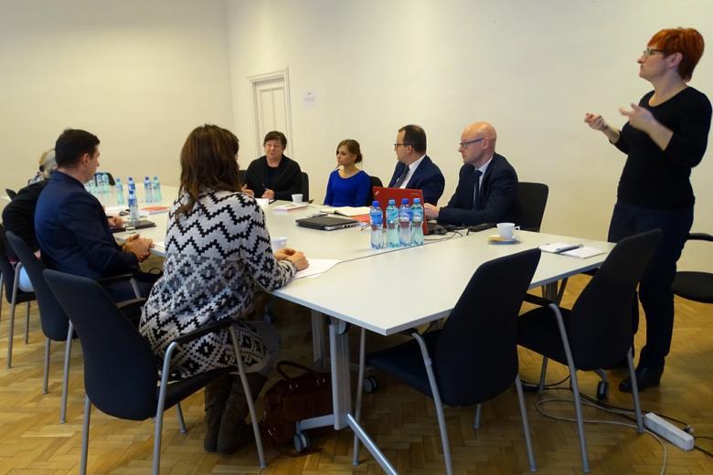 zdjęcie: przy białym stole siedzi kilka osób