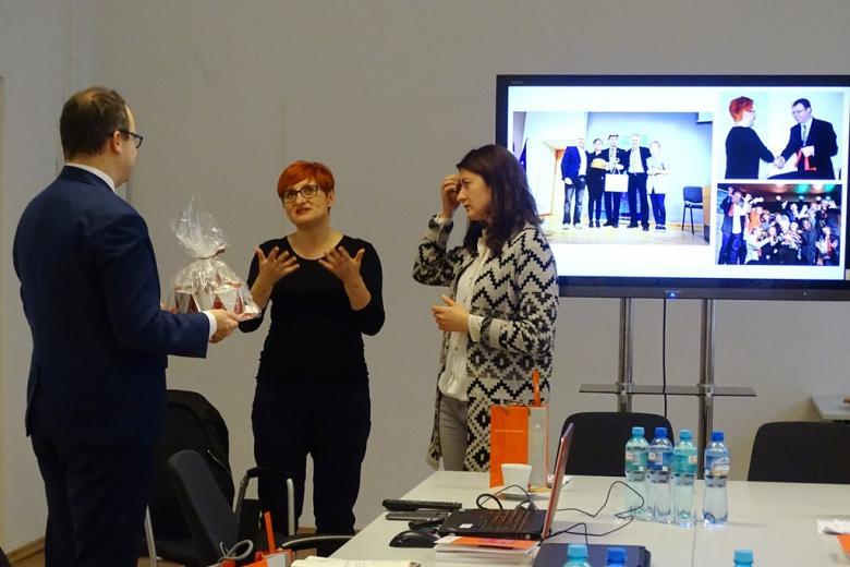zdjęcie: mężczyzna w garniturze trzyma prezent obok stoją dwie kobiety