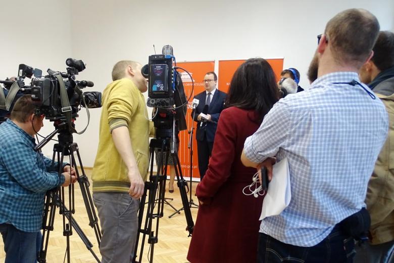 zdjęcie: na pierwszym planie tyłem stoi kilka osób, obok nich są kamery przed nimi widać mężczynę w garniturze