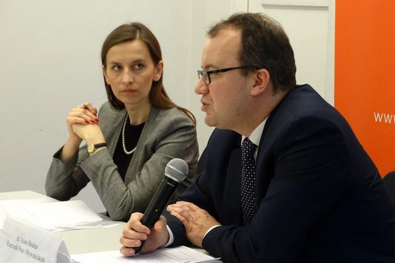 zdjęcie: mężczyzna jest ukazany z profilu, za nim siedzi kobieta, któta patrzy w jego stronę