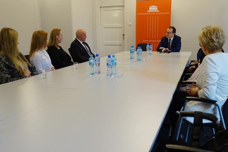 zdjęcie: kilka osón siedzi przy białym stole