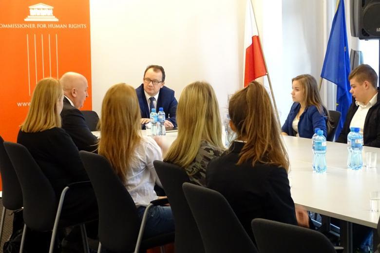 zdjęcie: przy białych, złączonych ze sobą stołach siedzi kilka osób