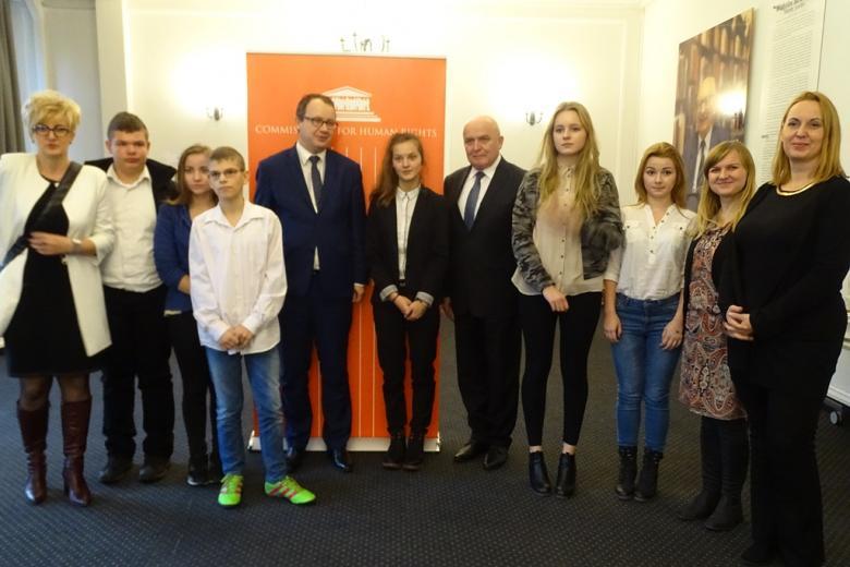 zdjęcie: kilka osób stoi przy pomarańczowym banerze