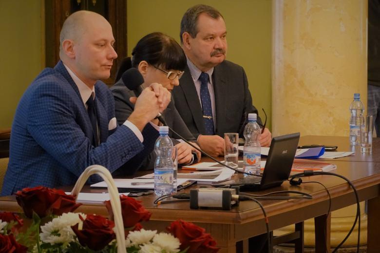 zdjęcie: dwaj mężczyźni i kobieta siedza przy stole przed nimi jest butek biało-czerwonych kwiatów