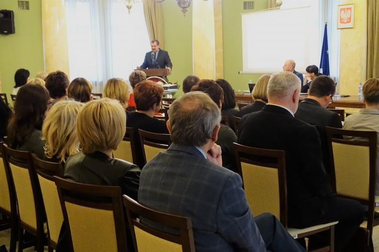 zdjęcie: w tle mężczyzna przy mównicy przed nimi kilkadziesiąt osób