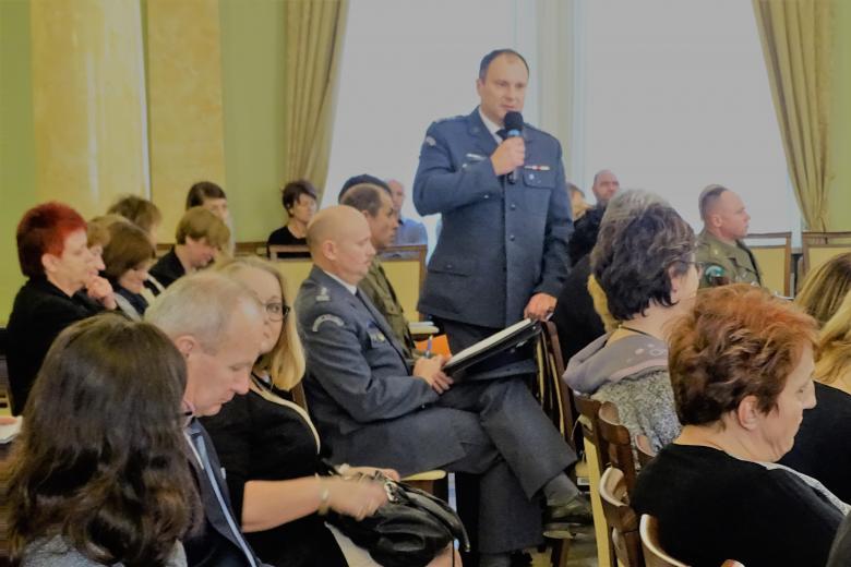 zdjęcie: mężczyzna w granatowym mundurze stoi, wokół niego inne osoby siedzą na krzesłach