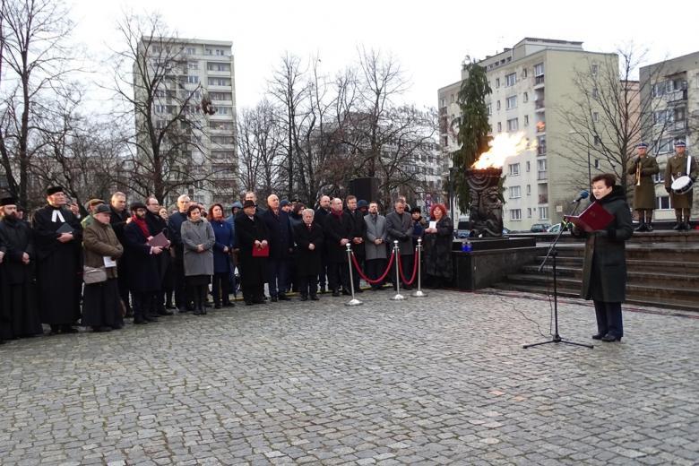 zdjęcie: przed pomnikiem przy mikrofonie stoi kobieta, obok stoi kilkadziesiąt osób