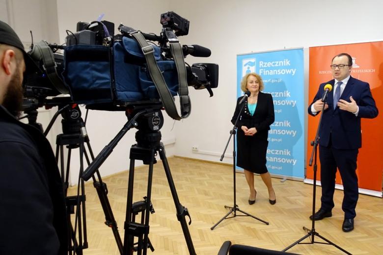 zdjęcie: na tle niebieskiego i pomarańczowego baneru stoją kobieta i mężczyzna