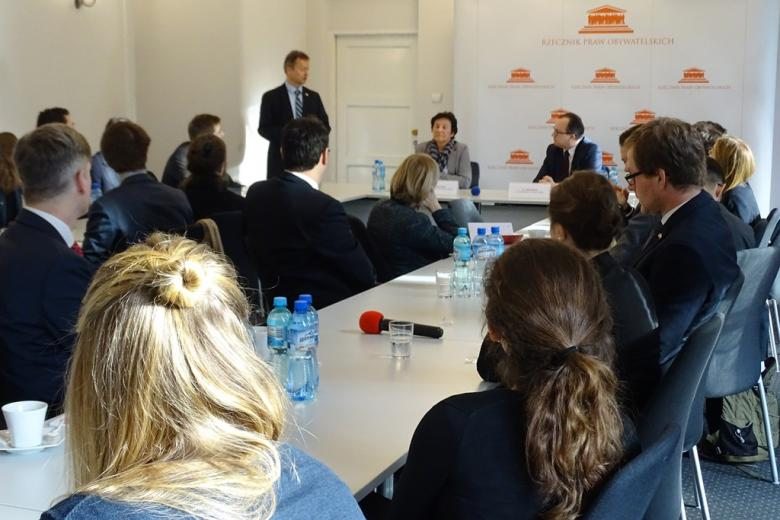 zdjęcie: kilka osób siedzi przy białych stołach, jeden z mężczyzn stoi