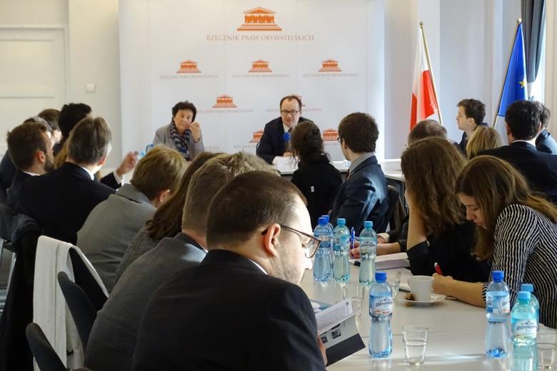 zdjęcie: kilka osób siedzi przy stołach, na wprost siedzi mężczyzna mówiący do mikrofonu