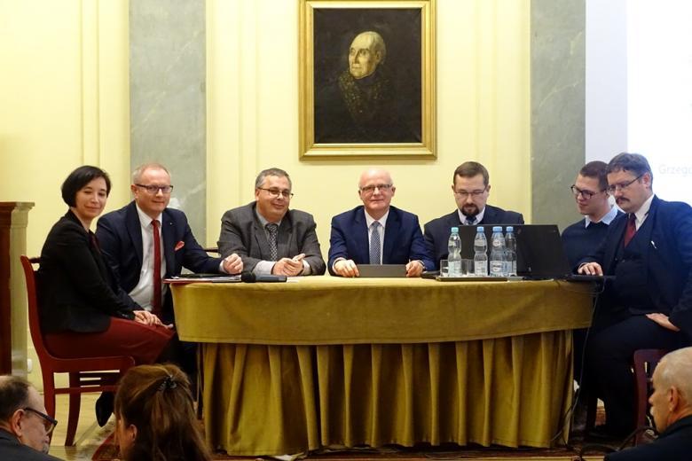 zdjęcie: klika osób siedzi za stołem, który jest na podwyższeniu