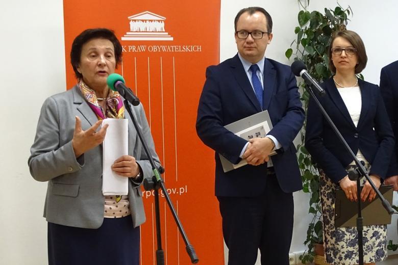 zdjęcie: przy mikrofonach stoją dwie kobiety i mężczyzna, jedna z kobiet mówi do mikrofonu