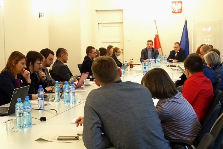 zdjęcie; kilkanaście osób siedzi przy pdłużnym białym stole i wpatruje się w dwóch mężczyzn siedzących u szczytu stołu