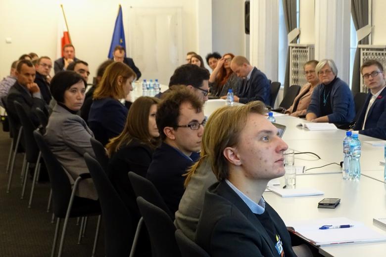 zdjęcie: kilkanaśie osób siedzi przy białym stole