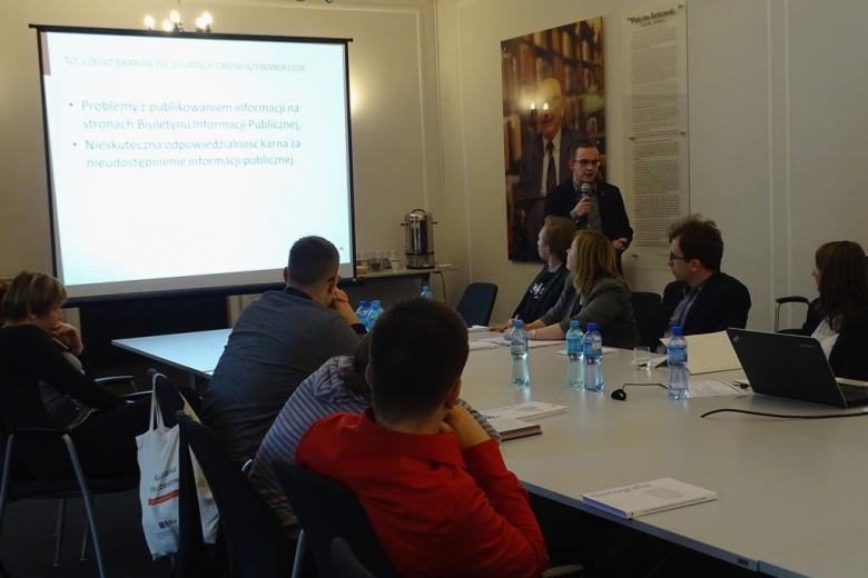 zdjęcie: po lewej stronie widać duży biąły ekran, obok niego stoi mężczyzna, przed nim widać kilka osób siedzących przy stole
