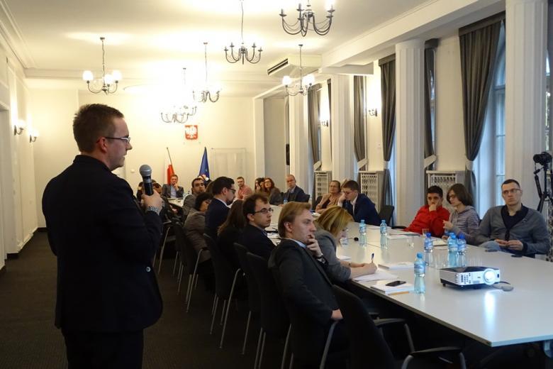 zdjęcie: mężczyzna na pierwszym planie stoi tyłem przed nimi kilkanaście osób siedzi przy stole