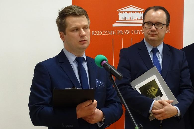zdjęcie: dwaj mężczyźni w garniturach, jeden z nich trzyma książkę
