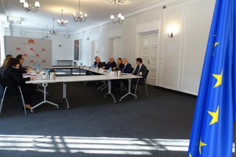 zdjęcie: po prawej stronie fragment flagi UE, w tle kilkanaście osób siedzi przy stole