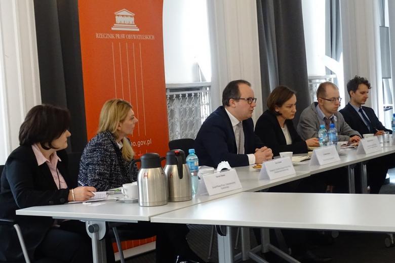 zdjęcie: kilka osób siedzi przy stole za nimi pomarańczowy baner